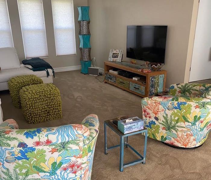 Living room with chairs on wet carpet