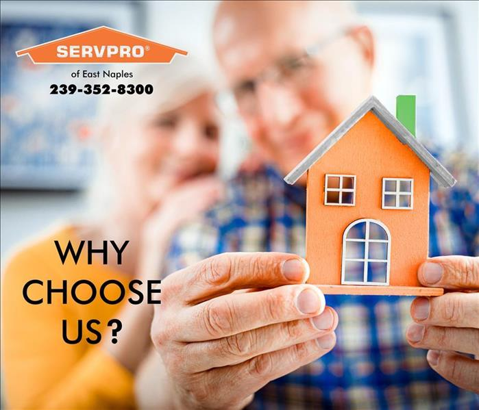 Old couple holding up a arts and crafts home with text asking Why SERVPRO?