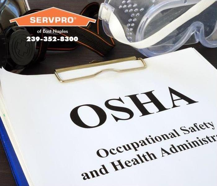 The letters OSHA written on a paper on a clipboard.